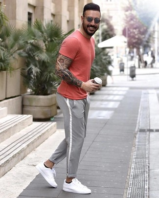 rotes T-Shirt mit einem Rundhalsausschnitt, graue Chinohose, weiße Leder niedrige Sneakers, graue Sonnenbrille für Herren