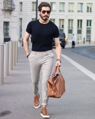 schwarzes T-Shirt mit einem Rundhalsausschnitt, hellbeige Chinohose, rotbraune Leder niedrige Sneakers, rotbraune Leder Reisetasche für Herren