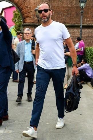 Dunkelblaue Chinohose kombinieren: trends 2020: Vereinigen Sie ein weißes T-Shirt mit einem Rundhalsausschnitt mit einer dunkelblauen Chinohose für ein großartiges Wochenend-Outfit. Weiße Leder niedrige Sneakers fügen sich nahtlos in einer Vielzahl von Outfits ein.