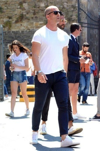 Weiße Leder niedrige Sneakers kombinieren für heiß Wetter: trends 2020: Tragen Sie ein weißes T-Shirt mit einem Rundhalsausschnitt und eine dunkelblaue Chinohose für einen bequemen Alltags-Look. Weiße Leder niedrige Sneakers sind eine großartige Wahl, um dieses Outfit zu vervollständigen.