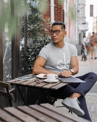 Weiße Leder niedrige Sneakers kombinieren – 405 Herren Outfits heiß Wetter: Tragen Sie ein graues bedrucktes T-Shirt mit einem Rundhalsausschnitt und eine dunkelblaue Chinohose für ein sonntägliches Mittagessen mit Freunden. Weiße Leder niedrige Sneakers sind eine gute Wahl, um dieses Outfit zu vervollständigen.