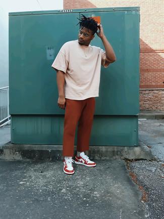 Weiße und rote Leder niedrige Sneakers kombinieren – 500+ Herren Outfits heiß Wetter: Kombinieren Sie ein hellbeige T-Shirt mit einem Rundhalsausschnitt mit einer rotbraunen Chinohose, um einen lockeren, aber dennoch stylischen Look zu erhalten. Dieses Outfit passt hervorragend zusammen mit weißen und roten Leder niedrigen Sneakers.