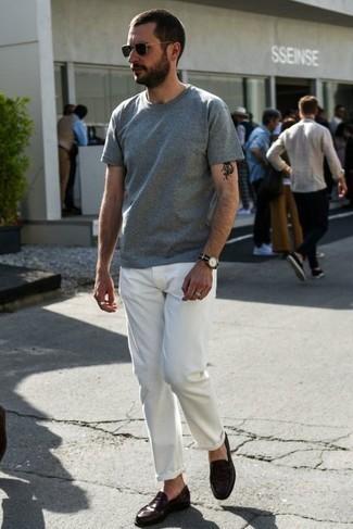 Dunkelbraune Leder Slipper kombinieren – 500+ Herren Outfits: Paaren Sie ein graues T-Shirt mit einem Rundhalsausschnitt mit einer weißen Chinohose, um mühelos alles zu meistern, was auch immer der Tag bringen mag. Dunkelbraune Leder Slipper bringen Eleganz zu einem ansonsten schlichten Look.