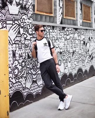 Wie kombinieren: weißes und schwarzes bedrucktes T-Shirt mit einem Rundhalsausschnitt, dunkelgraue Chinohose, weiße Sportschuhe, schwarzer Leder Rucksack