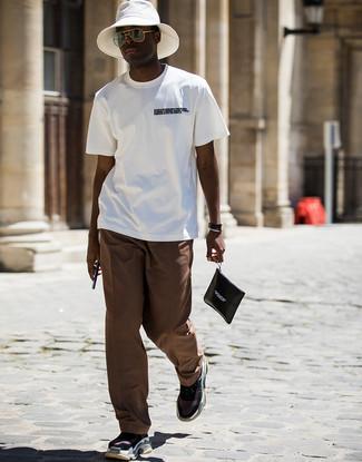 Weißen Fischerhut kombinieren: trends 2020: Für ein bequemes Couch-Outfit, erwägen Sie das Tragen von einem weißen und schwarzen bedruckten T-Shirt mit einem Rundhalsausschnitt und einem weißen Fischerhut. Setzen Sie bei den Schuhen auf die klassische Variante mit schwarzen Sportschuhen.