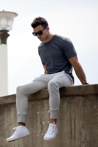 Wie kombinieren: dunkelgraues T-Shirt mit einem Rundhalsausschnitt, graue Jogginghose, weiße hohe Sneakers aus Leder, schwarze Sonnenbrille