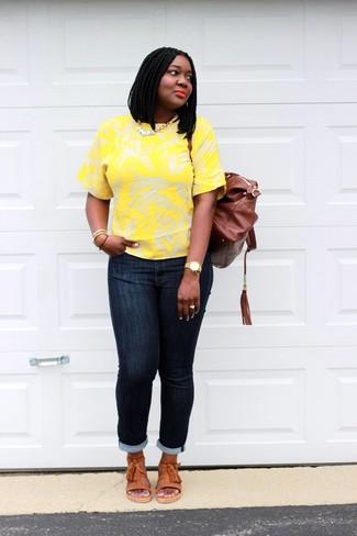 Wie kombinieren: gelbes T-Shirt mit einem Rundhalsausschnitt mit Blumenmuster, dunkelblaue enge Jeans, orange flache Sandalen aus Leder, brauner Leder Rucksack
