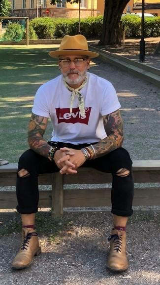 Wie kombinieren: weißes und rotes bedrucktes T-Shirt mit einem Rundhalsausschnitt, schwarze enge Jeans mit Destroyed-Effekten, beige Lederformelle stiefel, beige Wollhut