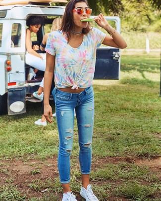 Wie kombinieren: mehrfarbiges Mit Batikmuster T-Shirt mit einem Rundhalsausschnitt, blaue enge Jeans mit Destroyed-Effekten, weiße hohe Sneakers aus Segeltuch, orange Sonnenbrille