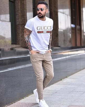 Wie kombinieren: weißes bedrucktes T-Shirt mit einem Rundhalsausschnitt, hellbeige enge Jeans, weiße Leder niedrige Sneakers, graue Sonnenbrille