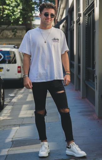 Schwarze enge Jeans mit Destroyed-Effekten kombinieren: trends 2020: Tragen Sie ein weißes bedrucktes T-Shirt mit einem Rundhalsausschnitt und schwarzen enge Jeans mit Destroyed-Effekten für einen entspannten Wochenend-Look. Fühlen Sie sich mutig? Entscheiden Sie sich für weißen und schwarzen Leder niedrige Sneakers.