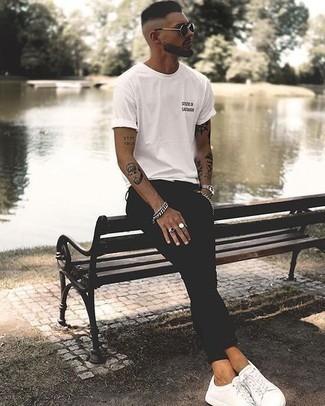 Herren Outfits & Modetrends 2020: lässige Outfits: Für ein bequemes Couch-Outfit, kombinieren Sie ein weißes und schwarzes bedrucktes T-Shirt mit einem Rundhalsausschnitt mit schwarzen engen Jeans. Fühlen Sie sich mutig? Entscheiden Sie sich für weißen Segeltuch niedrige Sneakers.