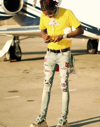 Wie kombinieren: gelbes bedrucktes T-Shirt mit einem Rundhalsausschnitt, hellblaue enge Jeans mit Destroyed-Effekten, beige Sportschuhe, schwarzer geflochtener Ledergürtel