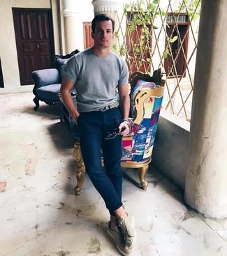 Wie kombinieren: graues Strick T-Shirt mit einem Rundhalsausschnitt, dunkelblaue Chinohose, hellbeige niedrige Sneakers, hellbeige Ledergürtel