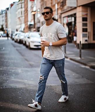 Wie kombinieren: graues bedrucktes T-Shirt mit einem Rundhalsausschnitt, blaue Jeans mit Destroyed-Effekten, weiße bedruckte Leder niedrige Sneakers, schwarze Sonnenbrille
