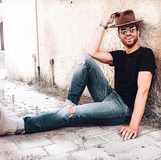 Wie kombinieren: schwarzes T-Shirt mit einem Rundhalsausschnitt, dunkelblaue Jeans mit Destroyed-Effekten, hellbeige Chelsea-Stiefel aus Wildleder, brauner Wollhut