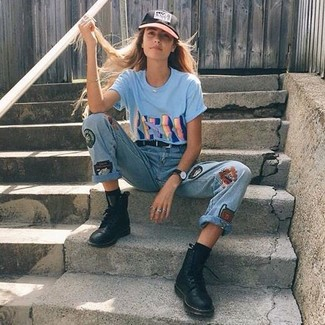 Wie kombinieren: hellblaues bedrucktes T-Shirt mit einem Rundhalsausschnitt, hellblaue bestickte Jeans, schwarze flache Stiefel mit einer Schnürung aus Leder, schwarze Baseballkappe