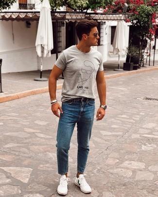 Weiße und grüne Leder niedrige Sneakers kombinieren – 43 Sommer Herren Outfits: Für ein bequemes Couch-Outfit, tragen Sie ein graues bedrucktes T-Shirt mit einem Rundhalsausschnitt und blauen Jeans. Weiße und grüne Leder niedrige Sneakers sind eine großartige Wahl, um dieses Outfit zu vervollständigen. Dieses Outfit eignet sich perfekt für den Sommer.