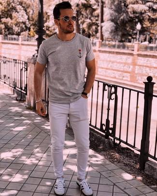 Wie kombinieren: graues bedrucktes T-Shirt mit einem Rundhalsausschnitt, weiße Jeans, weiße und schwarze Sportschuhe, dunkelgraue Sonnenbrille