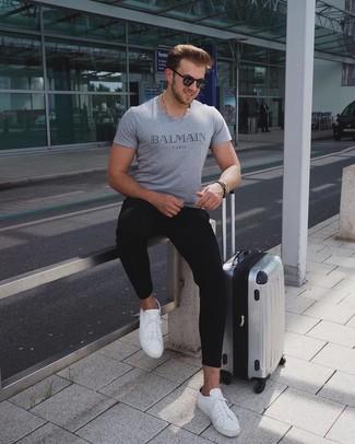 Wie kombinieren: graues bedrucktes T-Shirt mit einem Rundhalsausschnitt, schwarze Jogginghose, weiße Leder niedrige Sneakers, silberner Koffer