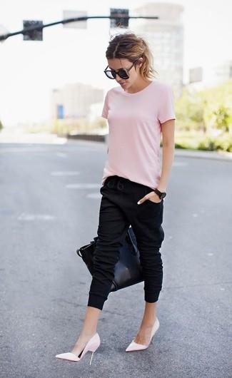 Wie kombinieren: rosa T-Shirt mit einem Rundhalsausschnitt, schwarze Jogginghose, rosa Leder Pumps, schwarze Shopper Tasche aus Leder
