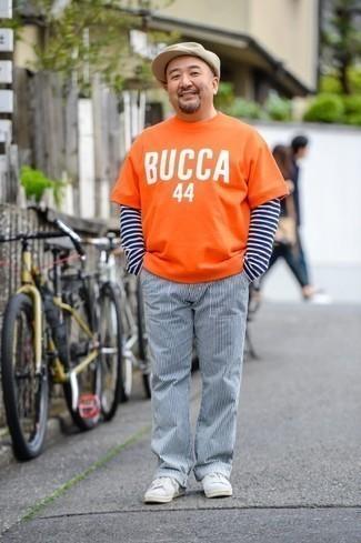 Graue Wildleder niedrige Sneakers kombinieren: trends 2020: Entscheiden Sie sich für ein orange bedrucktes T-Shirt mit einem Rundhalsausschnitt und eine weiße und dunkelblaue vertikal gestreifte Chinohose für einen entspannten Wochenend-Look. Graue Wildleder niedrige Sneakers sind eine gute Wahl, um dieses Outfit zu vervollständigen.