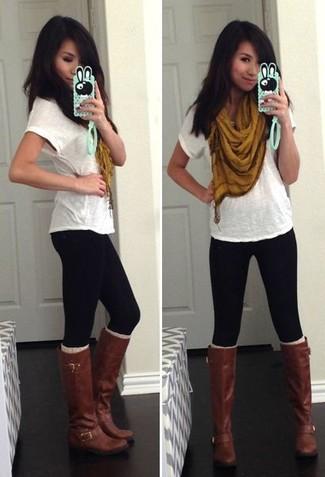 Wie kombinieren: weißes T-Shirt mit einem Rundhalsausschnitt, schwarze Leggings, dunkelbraune kniehohe Stiefel aus Leder, senf Schal