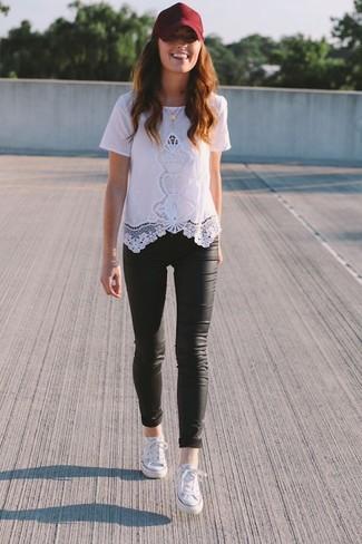 Wie kombinieren: weißes Spitze T-Shirt mit einem Rundhalsausschnitt, schwarze Lederleggings, weiße niedrige Sneakers, dunkelrote Baseballkappe