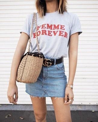 Wie kombinieren: graues bedrucktes T-Shirt mit einem Rundhalsausschnitt, hellblauer Jeans Minirock, beige Shopper Tasche aus Stroh, schwarzer Ledergürtel