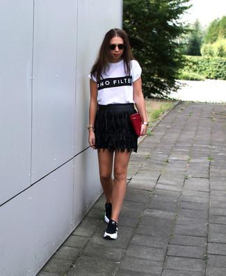 Wie kombinieren: weißes und schwarzes bedrucktes T-Shirt mit einem Rundhalsausschnitt, schwarzer Fransen Leder Minirock, schwarze und weiße Sportschuhe, dunkelrote Leder Clutch