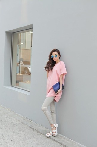 Wie kombinieren: rosa T-Shirt mit einem Rundhalsausschnitt, graue enge Hose, weiße Römersandalen, blaue Leder Clutch