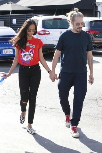 Wie kombinieren: rotes bedrucktes T-Shirt mit einem Rundhalsausschnitt, schwarze enge Jeans mit Destroyed-Effekten, weiße Slipper aus Kalbshaar mit Leopardenmuster, braune Sonnenbrille