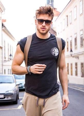 Wie kombinieren: schwarzes T-Shirt mit einem Rundhalsausschnitt, hellbeige Jogginghose, brauner Segeltuch Rucksack, dunkelbraune Sonnenbrille