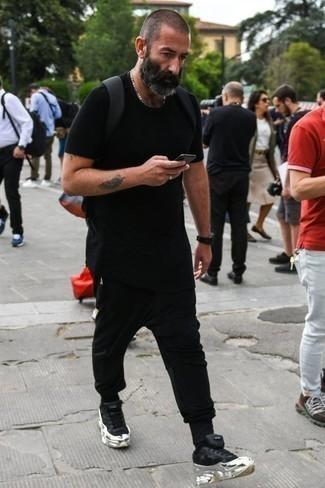 Schwarze Jogginghose kombinieren: lässige Outfits: trends 2020: Kombinieren Sie ein schwarzes T-Shirt mit einem Rundhalsausschnitt mit einer schwarzen Jogginghose für einen entspannten Wochenend-Look. Komplettieren Sie Ihr Outfit mit schwarzen Sportschuhen.