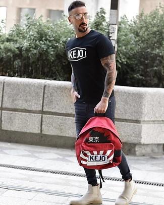 Wie kombinieren: schwarzes und weißes bedrucktes T-Shirt mit einem Rundhalsausschnitt, dunkelgraue enge Jeans, hellbeige Chelsea-Stiefel aus Wildleder, roter bedruckter Rucksack