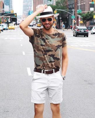 Wie kombinieren: olivgrünes Camouflage T-Shirt mit einem Rundhalsausschnitt, weiße Shorts, weißer Strohhut, dunkelbrauner Ledergürtel