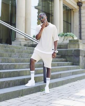 Wie kombinieren: hellbeige T-Shirt mit einem Rundhalsausschnitt, hellbeige Shorts, weiße niedrige Sneakers, dunkelblaue Sonnenbrille