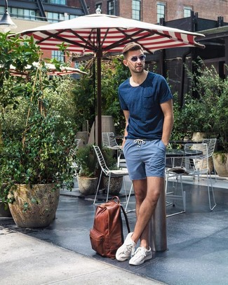 Wie kombinieren: dunkelblaues T-Shirt mit einem Rundhalsausschnitt, blaue Shorts, weiße niedrige Sneakers, brauner Leder Rucksack