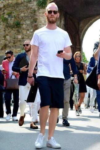 Weiße Leder niedrige Sneakers kombinieren für heiß Wetter: trends 2020: Entscheiden Sie sich für ein weißes T-Shirt mit einem Rundhalsausschnitt und dunkelblauen Shorts für ein bequemes Outfit, das außerdem gut zusammen passt. Komplettieren Sie Ihr Outfit mit weißen Leder niedrigen Sneakers.