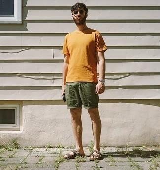 Lässige Outfits Herren 2020: Erwägen Sie das Tragen von einem orange T-Shirt mit einem Rundhalsausschnitt und olivgrünen Shorts für einen bequemen Alltags-Look. Fühlen Sie sich ideenreich? Ergänzen Sie Ihr Outfit mit braunen Ledersandalen.