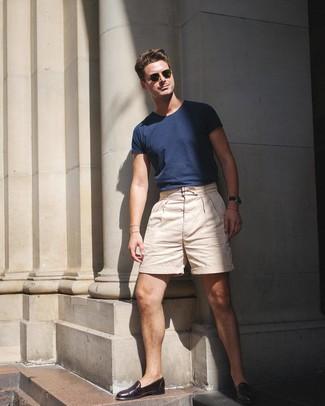 Wie kombinieren: dunkelblaues T-Shirt mit einem Rundhalsausschnitt, hellbeige Shorts, dunkelbraune Leder Slipper, olivgrüne Sonnenbrille