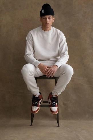 Trainingsanzug kombinieren: trends 2020: Für ein bequemes Couch-Outfit, erwägen Sie das Tragen von einem Trainingsanzug und einem weißen T-Shirt mit einem Rundhalsausschnitt. Ergänzen Sie Ihr Look mit weißen und roten hohen Sneakers aus Leder.