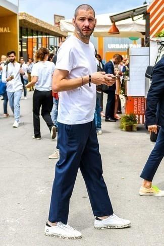 Dunkelblaue Chinohose kombinieren: trends 2020: Kombinieren Sie ein weißes T-Shirt mit einem Rundhalsausschnitt mit einer dunkelblauen Chinohose, um mühelos alles zu meistern, was auch immer der Tag bringen mag. Vervollständigen Sie Ihr Look mit weißen und schwarzen Leder niedrigen Sneakers.