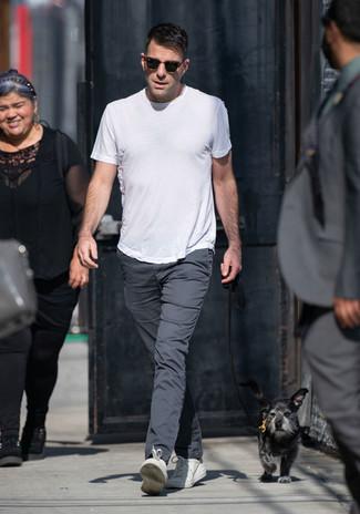 Wie kombinieren: weißes T-Shirt mit einem Rundhalsausschnitt, dunkelgraue Chinohose, weiße Leder niedrige Sneakers, dunkelbraune Sonnenbrille