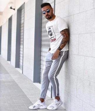Wie kombinieren: weißes bedrucktes T-Shirt mit einem Rundhalsausschnitt, graue Chinohose, weiße Sportschuhe, dunkelblaue Sonnenbrille