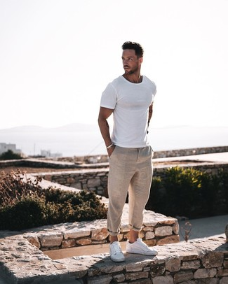 Wie kombinieren: weißes T-Shirt mit einem Rundhalsausschnitt, hellbeige Leinen Chinohose, weiße Leder niedrige Sneakers, silbernes Armband