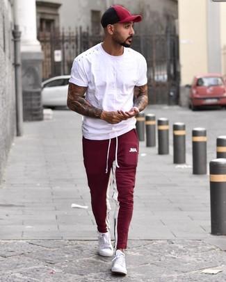 Wie kombinieren: weißes T-Shirt mit einem Rundhalsausschnitt, dunkelrote Jogginghose, weiße niedrige Sneakers, dunkelrote Baseballkappe