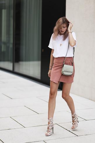 Rosa Wildleder Minirock kombinieren: trends 2020: Probieren Sie diese Kombination aus einem weißen T-Shirt mit einem Rundhalsausschnitt und einem rosa Wildleder Minirock, um einen genialen lässigen Look zu zaubern. Komplettieren Sie Ihr Outfit mit hellbeige Leder Sandaletten.