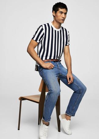 Weiße Leder niedrige Sneakers kombinieren: trends 2020: Ein weißes und dunkelblaues vertikal gestreiftes T-Shirt mit einem Rundhalsausschnitt und blaue Jeans sind eine kluge Outfit-Formel für Ihre Sammlung. Ergänzen Sie Ihr Look mit weißen Leder niedrigen Sneakers.