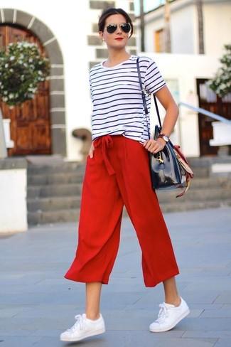 Wie kombinieren: weißes und schwarzes horizontal gestreiftes T-Shirt mit einem Rundhalsausschnitt, roter Hosenrock, weiße Leder niedrige Sneakers, dunkelblaue Shopper Tasche aus Leder